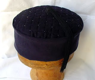 an example of a handmade navy smoking cap, with a quilted and beaded tip and hand crafted vintage tassel.